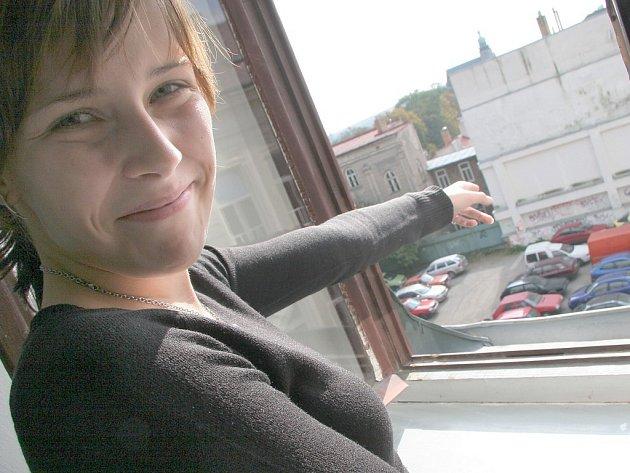 Lenka Drahozalová, studentka grafické školy, ukazuje, které parkoviště v Křížové ulici bude zrušeno. Místo něj má vyrůst bytový dům.