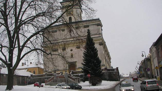 Sníh na Sezimově náměstí zakryl hrubou stylovou dlažbu nových chodníků. V pozadí dominanta centra Polné. Chrám čekají venkovní stavební úpravy.