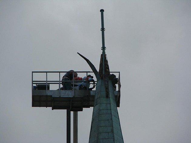 Klempíři v sobotu odpoledne vracejí kříž na věž kostela svaté Kateřiny Sienské.