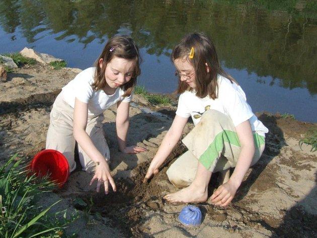 Dcery Edity Melicharové si hrají na hrázi rybníka.
