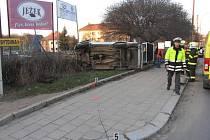 Policejní auto skončilo po srážce na boku mimo silnici
