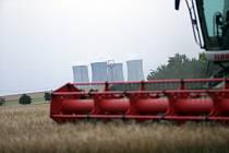 Zlátnoucí obilí měnící se ve strniště je symbolem letních prázdnin. Kombajny vyrazily na pole, jehož kulisou jsou chladící věže dukovanské jaderné elektrárny.