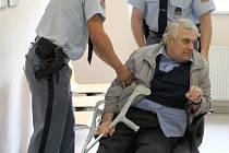 Justiční stráž odváží ze soudní síně Františka Fialu, který po rozsudku upadl a nemohl se hýbat.