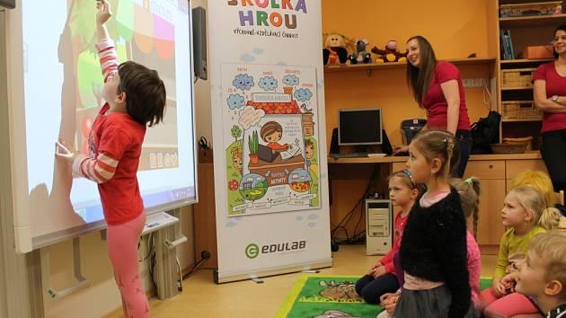 Počty. Kolik jablek přesunout z košíku do stánku se zeleninou, radí dětem v mateřské školce Březinova nápověda, kterou si zapnou pomocí interaktivní tabule. Počítání dětem jde. Někteří předškoláci bojují spíše s velikostí tabule.