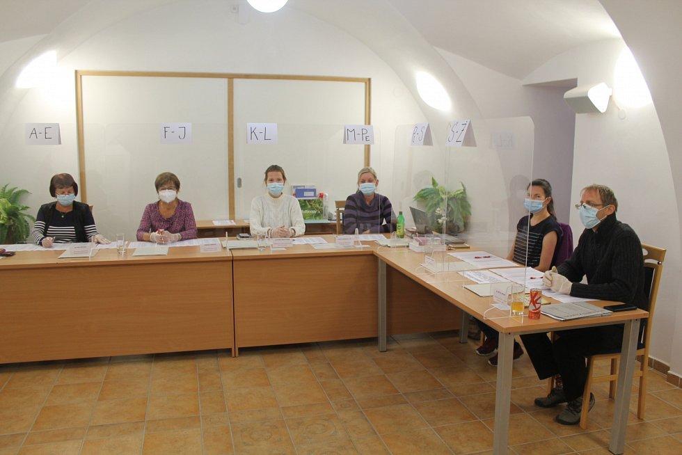 Za plexisklem sedí volební komise v Lukách nad Jihlavou.