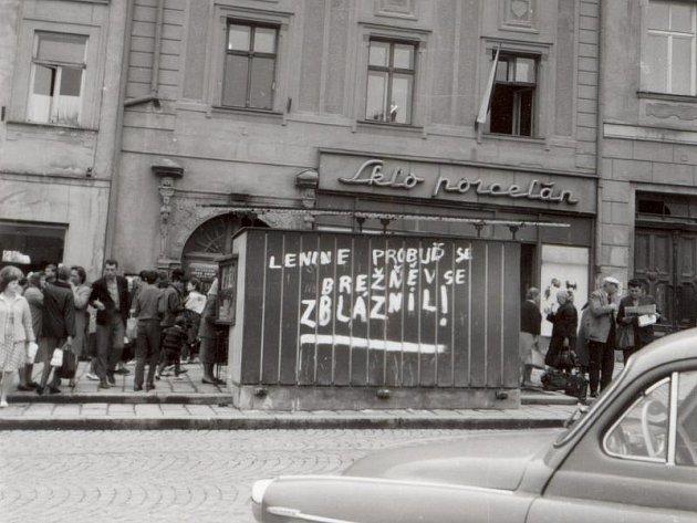 Srocení davu s nákupními taškami před samoobsluhou s potravinami na tehdejším Náměstí míru (dnes Masarykovo náměstí). Na trafice je zachycen jeden ze stovek nápisů ve městě.