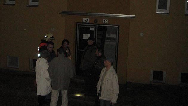 Hasiči se před domem, ve kterém v pátek hořelo, pokoušeli uklidňovat vystrašené sousedy.