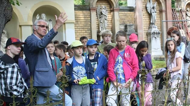 Předseda Spolku pro starou Jihlavu Vilém Wodák (na snímku uprostřed) pořádá vycházky po jihlavském Ústředním hřbitově pro veřejnost i pro školy. Přítomným přibližuje zemřelé jihlavské osobnosti u jejich hrobů.