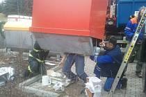 Teprve když nastoupila do akce speciální hydraulická ruka, objevily se pod červeným kontejnerem mladíkovy nohy.