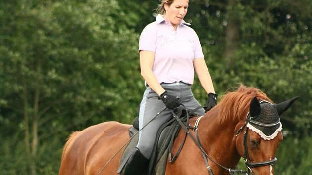 Manželka Andrea Vejmělková při tréninku projíždí kolbiště na koni Guliverovi z vlastního chovu.