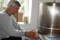 Jiří Sláma stáčí z nerezové soupravy med do skleniček s vlastní etiketou.