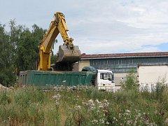 Bagr složila z podvalníku stavební firma na pozemku někdejší továrny o víkendu. V pondělí se lžíce stroje zakousla do země a mění zaplevelenou parcelu k nepoznání.