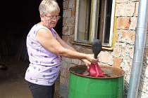 """Sudy pomáhají. Téměř každá domácnost v Suché zachytává """"nedostatkové zboží"""" – dešťovou vodu – do sudů. Alena Doležalová z jednoho barelu nabírá vodu na zalévání."""