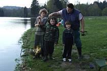 Na břehu Plodového rybníka při cestě ke kempu Velkopařezitý otcům často pomáhají rybařit děti.