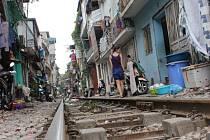 V jedné vietnamské uličce projížděl vlak. Kolej byla asi metr od pahů domů.