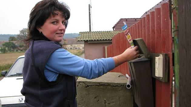 Schránky jsou věčně hladové. Doručovatelka Miluše Krejčová vhazuje tiskoviny do schránky domu na okraji Žatce. Do vzdálených částí zajíždějí doručovatelé na závěr roznášky.