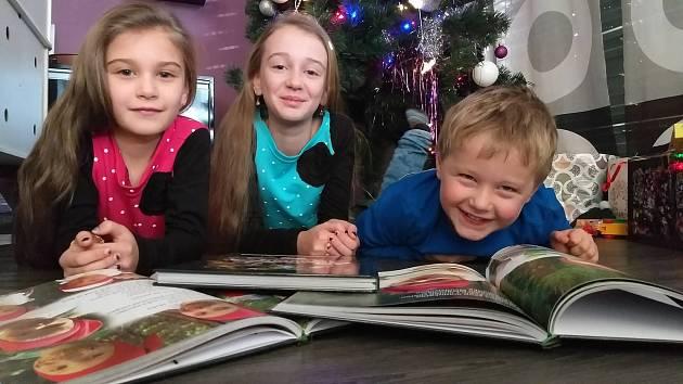Děti se radují z dárečku v podobě knížiky.