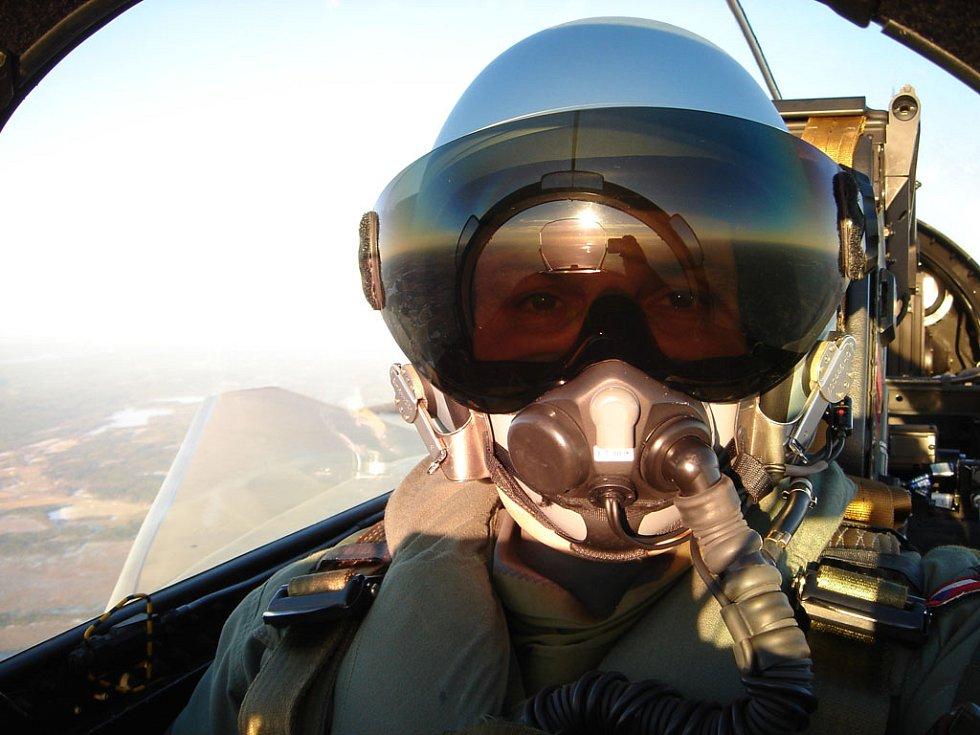 Počasí tentokrát pilotovi Gripenu Michaelu Borůvkovi při focení přálo. Snímek zachycuje desítky kilometrů krajiny pod letadlem. Na tmavých brýlích je vidět odraz slunečního kotouče, obřího displeje nad palubní deskou a pilotova ruka s fotoaparátem.