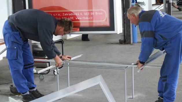 Dělníci instalují nové zábrany na autobusovém nádraží v Jihlavě, které by měly zabránit slepcům ve srážce s reklamními tabulemi.
