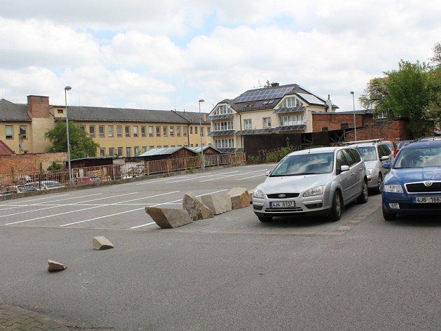 Na snímku je plocha v Havlíčkově ulici pod starou Billou. Půlka patří Kohnovým. Ta je v současnosti prázdná, protože ji majitelé připravují na zpoplatnění. Druhá polovina je města, tam auta stát mohou.