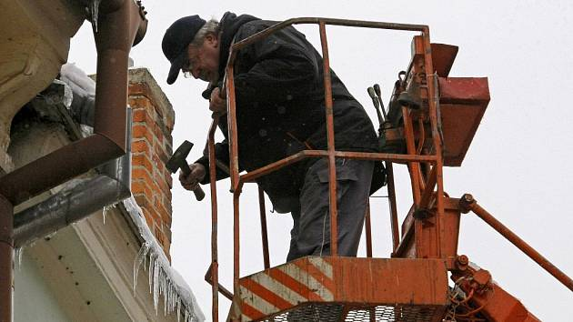 Klempířská firma odstraňuje rampouchy ze střech.