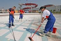 Pracovníci čistí venkovní bazén. Archivní foto.