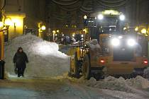 Velký nakladač na snímku právě nahrnuje sníh na hromadu v křižovatce Benešovy a Palackého ulice.