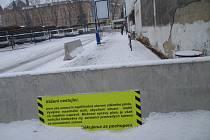 Zděný plot na autobusovém nádraží je ve špatném stavu. Omítka opadává a zeď se nahýbá.