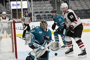 Brankář San Jose Josef Kořenář v utkání proti Arizoně, ve kterém si připsal svoji první výhru v NHL, zasahuje před Michaelem Buntingem.