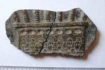 Kovové zlomky. Vyhrabali je chlapci hokejkami z pískoviště. Jsou téměř k nerozeznání od fragmentů staroegyptského reliéfu, přitom jde o odlitek z čistého zinku.