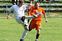 Polenský kapitán Aleš Frolda odkopává míč do bezpečí. V tomto okamžiku ještě hosté Davida Jirgla (vpravo) ubránili. Hartvíkovický kanonýr však nakonec, byť ze sporné situace, utkání rozhodl.