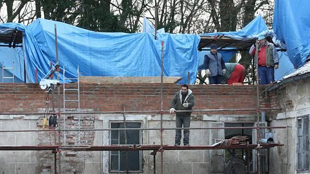 Dělníci dokončují římsu a začínají stavět krov, který bude prozatím provizorně přetažený plachtou.