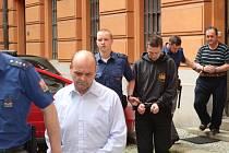 Trojici Karel Dubský, Josef Dubský mladší a Josef Dubský starší přivádí eskorta do jednací místnosti Krajského soudu v Brně.