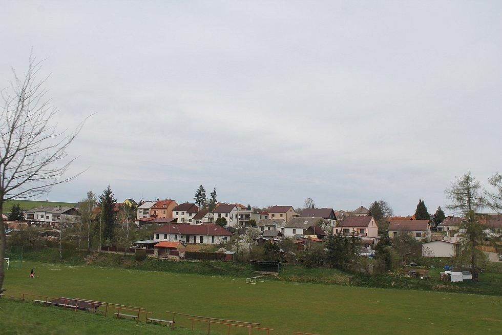 Domky nad fotbalovým hřištěm na kraji města.