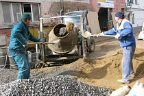 Parta zedníků se nezastaví. Dva nahoře míchají beton, v jámě hluboko pod terénem další zpevňují základy a pracují na desítkách stavebních prvků.