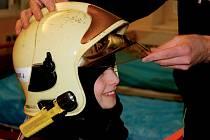 Děti si zkoušely hasičskou helmu.