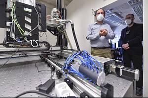 Michal Vopálenský (druhý zprava) z laboratoře rentgenové tomografie Ústavu teoretické a aplikované mechaniky Akademie věd v Telči a ředitel telčského centra Jakub Novotný (vpravo) představují metodu rychlého snímkování pomocí speciálního tomografu.