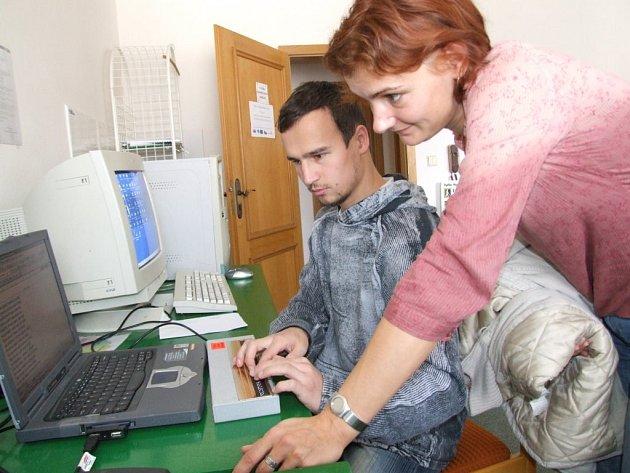 Věra Koudelková z radnice ve Žďáru nad Sázavou si prohlíží novinku – počítač s výstupem ke čtení plastického Braillova písma.