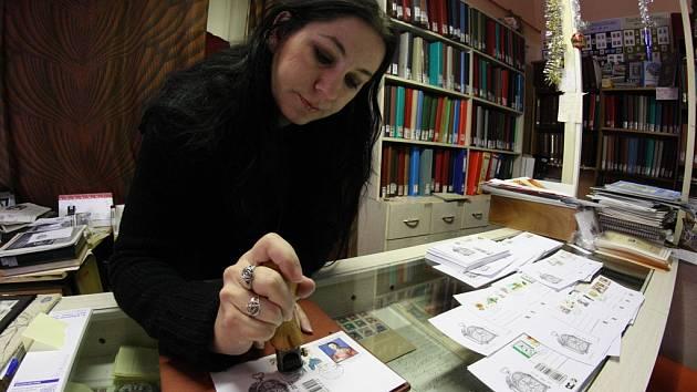Pracovnice jihlavské Poštovny Blanka Urbanová razítkuje dopisnice razítkem se samými dvanáctkami.