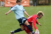 Zbytečná snaha. Třebíčský útočník Roman Durajka (v červeném dresu) padá k zemi po zákroku jednoho z hulínských fotbalistů. HFK na domácím trávníku vyšel naprázdno, prohrál 0:1.