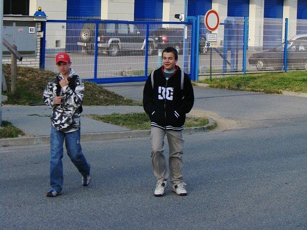 Chodci chodí přes Vrchlického ulici tam, kde zebra není. Křižují silnici hned za výjezdem sanitek.