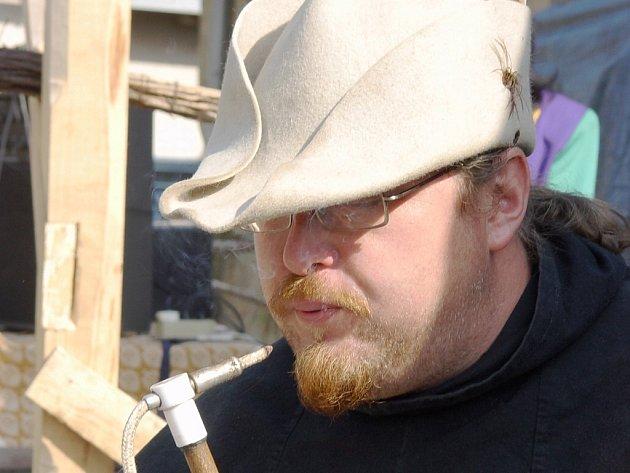 Dělmistr David Kočka je od černého řemesla a k železu má blízko. Na snímku drží před odpálením rány žhnoucí doutnák, kterým se zapaluje černý prach v hlavni.