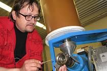 Lis na olej v biofarmě Sasov potřebuje zahřát na provozní teplotu, aby byl olej co nejkvalitnější a pokrutiny vypadávaly v podobě tužších špalíků. Josef Sklenář seřizuje část, z níž padají vylisované zbytky.