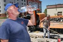 Osvěžení při náročné práci. Ne všichni mají možnost luxusu klimatizovaných kanceláří. Těm, kteří pracují venku, musí v horkých dnech stačit lahev vody a krátká pauza ve stínu.