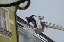 V pondělí pracovníci na Benešově ulici v Jihlavě shazovali nebezpečně převisy sněhu. Na pomoc musela přijet i speciální technika v podobě vysokozdvižné plošiny.