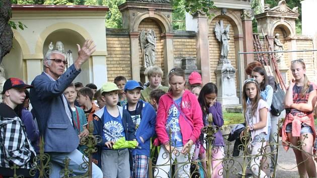 Vilém Wodák dětem přibližuje Leopolda Fritze, jihlavského lékaře a lidumila. Zasloužil se mimo jiné o založení ústředního hřbitova. Na snímku stojí skupina za dělicí stěnou před pomníkem Gottlieba Czapa, předního jihlavského podnikatele a průmyslníka.