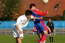 Borovinský Vojtěch Štěpnička (v bílém) prohrává vzdušný souboj s hartvíkovickým Milošem Neumannem. Hosté v derby vyhráli jasně 4:1.