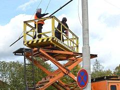 Výstavba nové trolejbusové tratě ve Vrchlického ulici v Jihlavě v úseku mezi Domem zdraví a Horním Kosovem. Dělníci uchycují na stožáry výložníky, na nichž pak bude viset trolejové vedení.