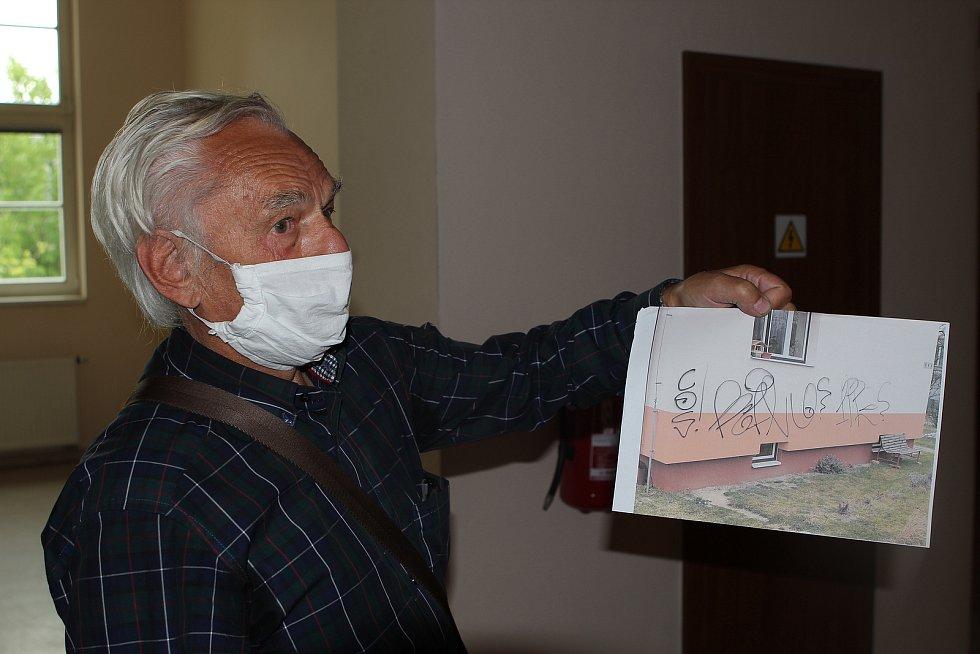 MIloš Fiala ukazuje na fotografii počmáraný dům v Jihlavě.