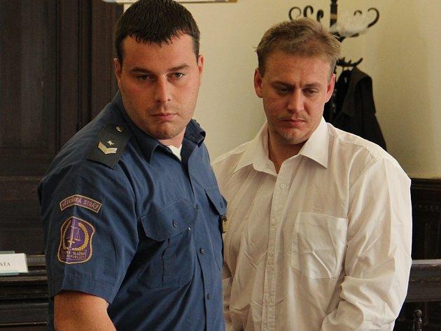 Policista odvádí Jaroslava Kafku od soudu. Snímek je ze soudního líčení, které se konalo loni v říjnu.